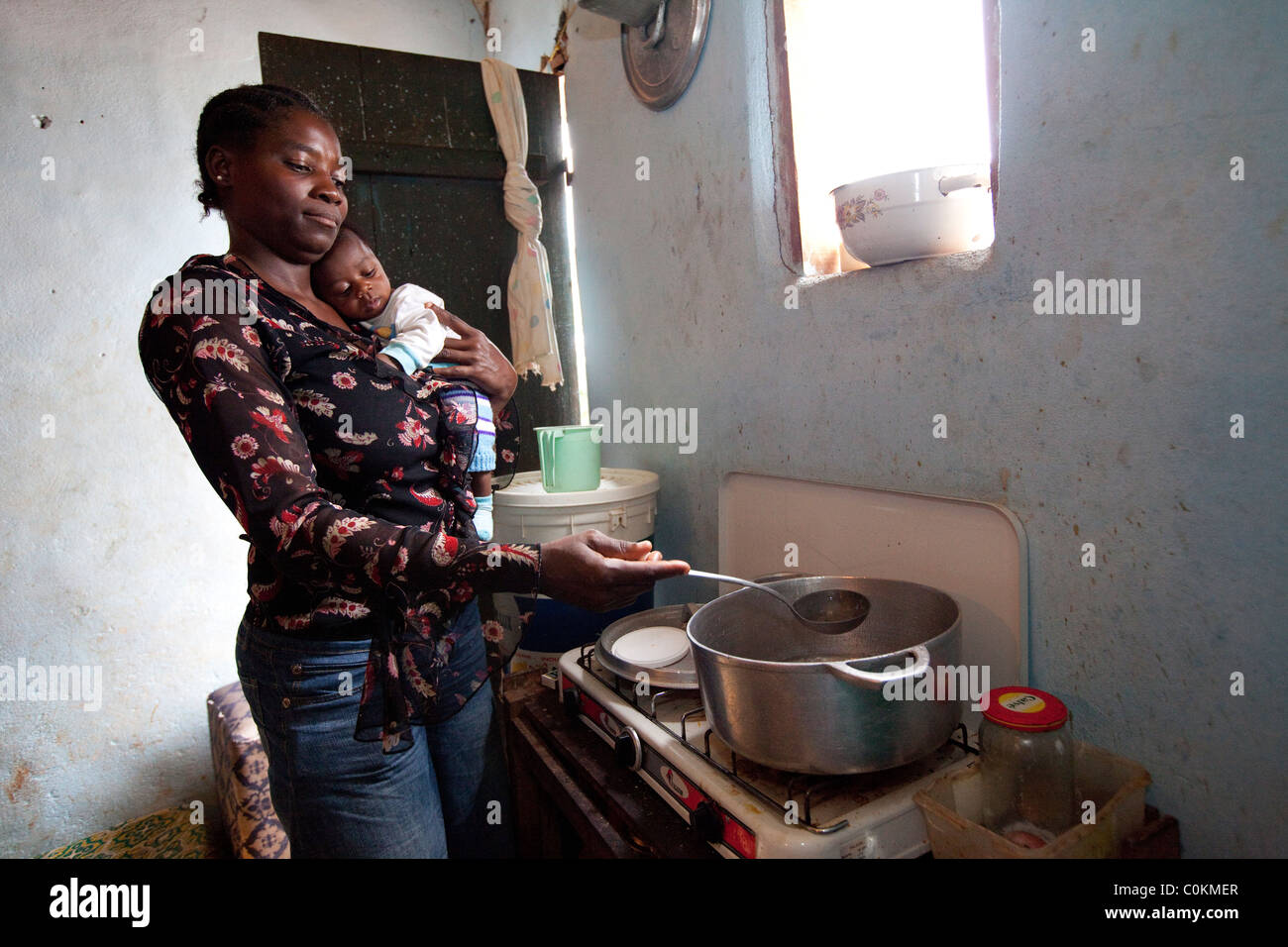 A single mother holds her 3 month old baby boy while cooking at her home in Yaounde, Cameroon, West Africa. - Stock Image