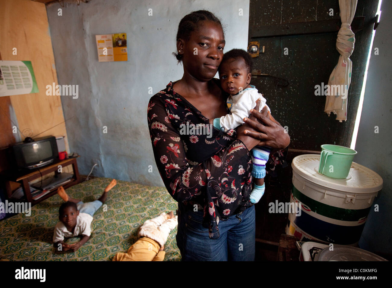 A young single mother stands in her one room apartment in Yaounde, Cameroon, West Africa. - Stock Image