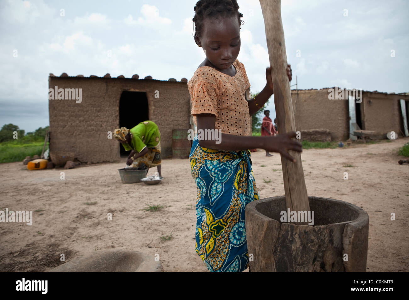 A young girl grinds peanuts into peanut butter in Safo, Mali, West Africa. - Stock Image
