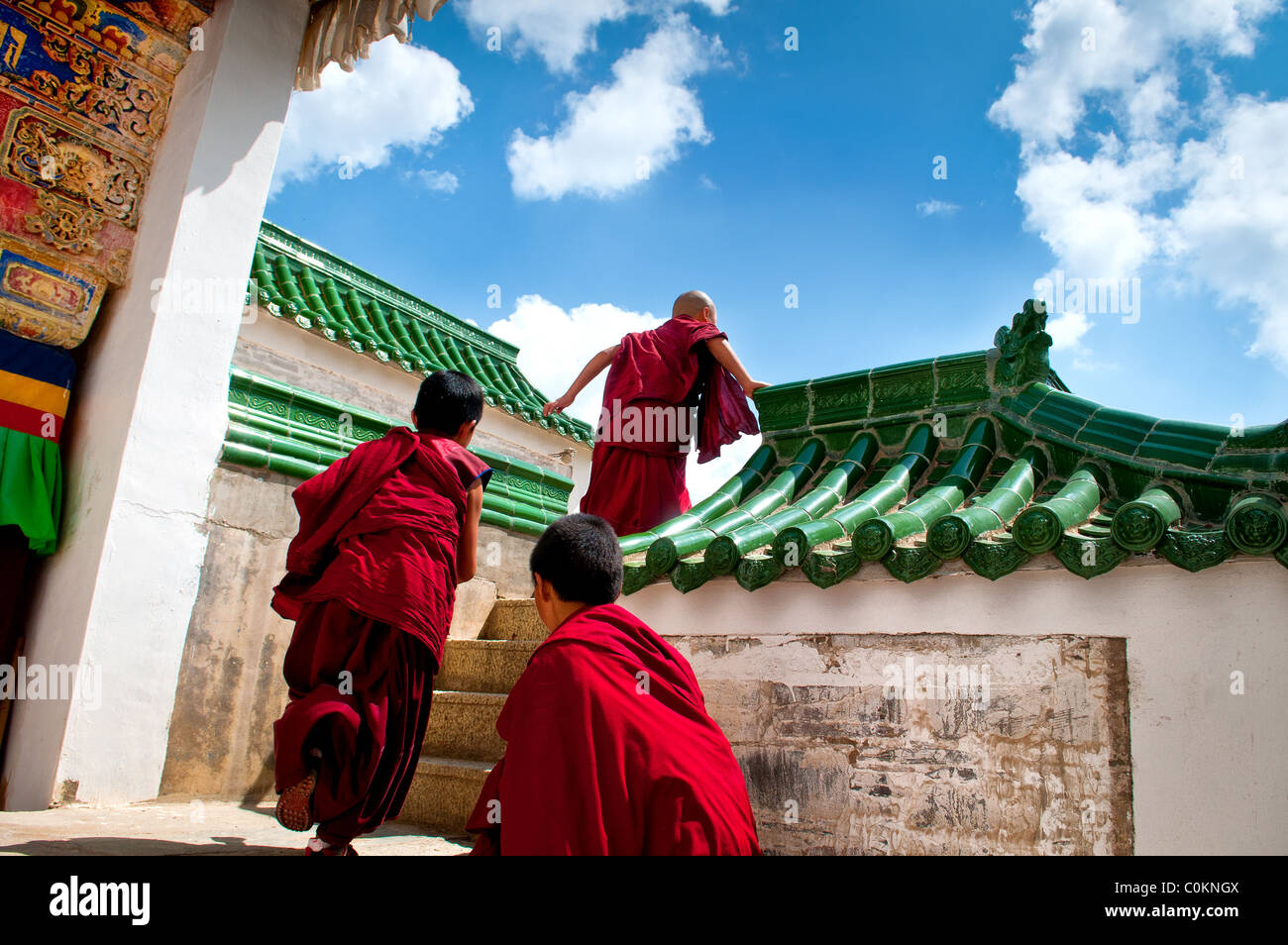 Young tibetan novice monks running in Labrang Monastery Stock Photo