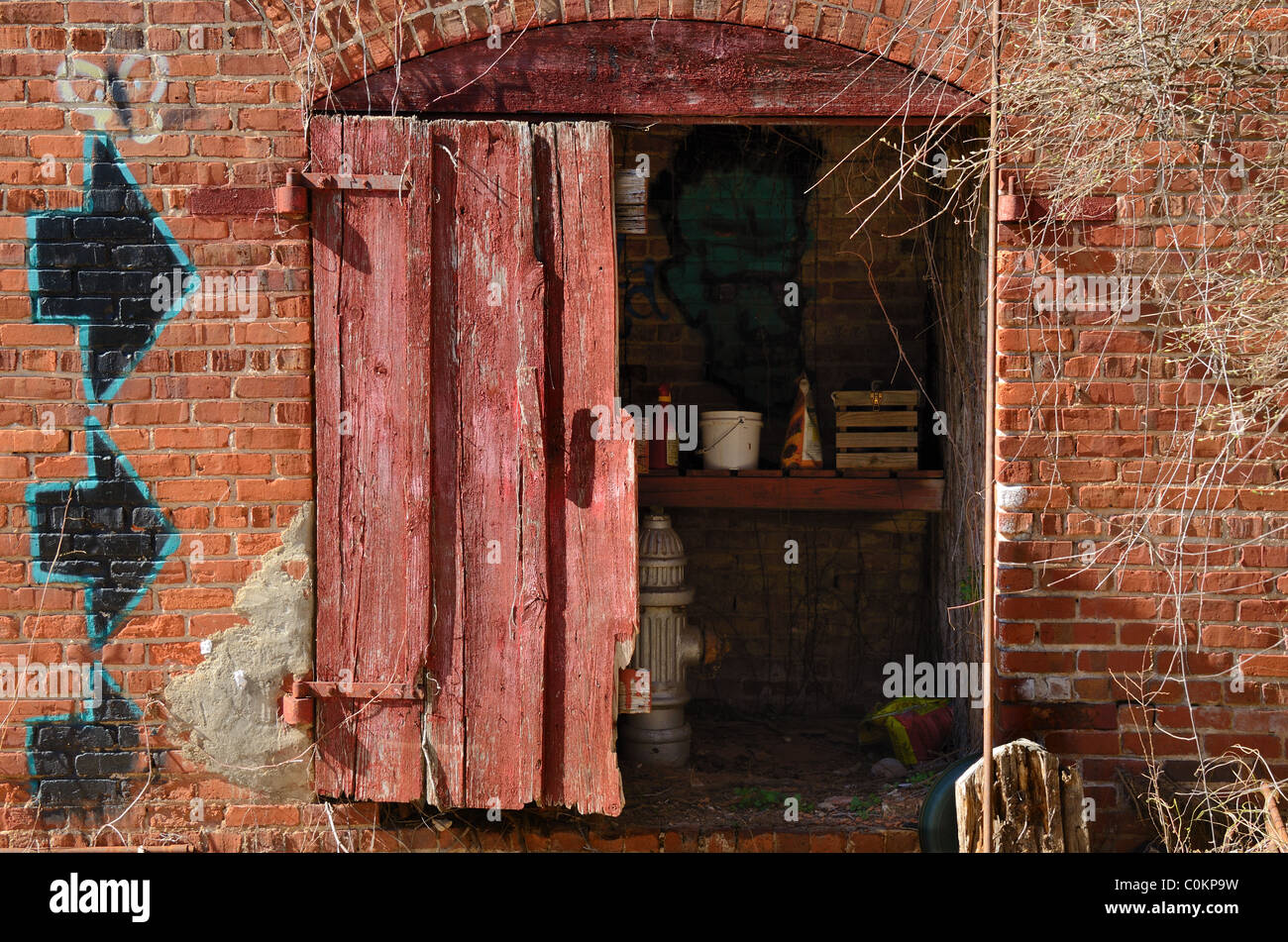 A gritty brick shed with graffiti - Stock Image