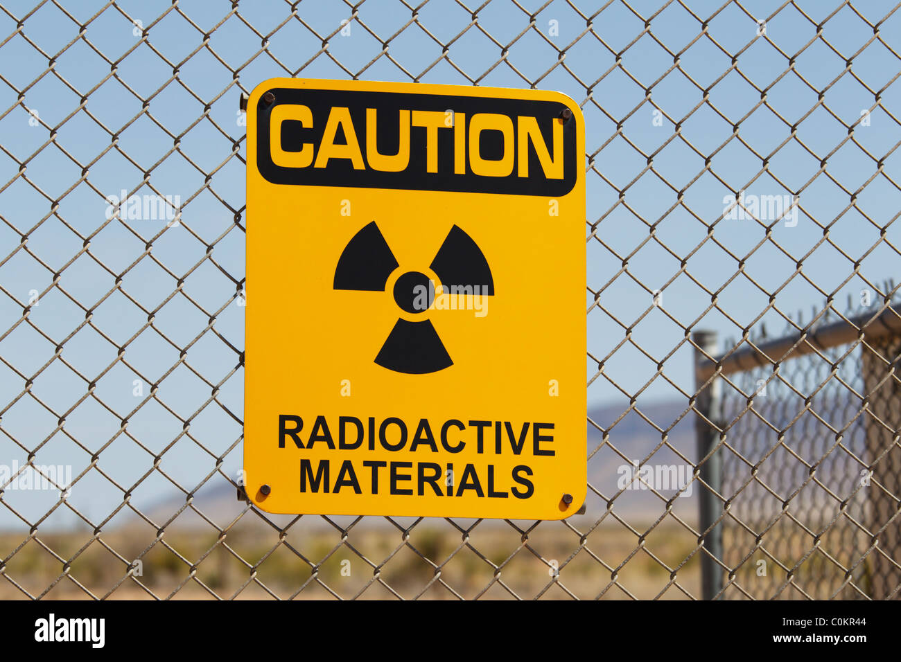 A Caution Radioactive Materials sign on a wire fence, Trinity Site, New Mexico. - Stock Image