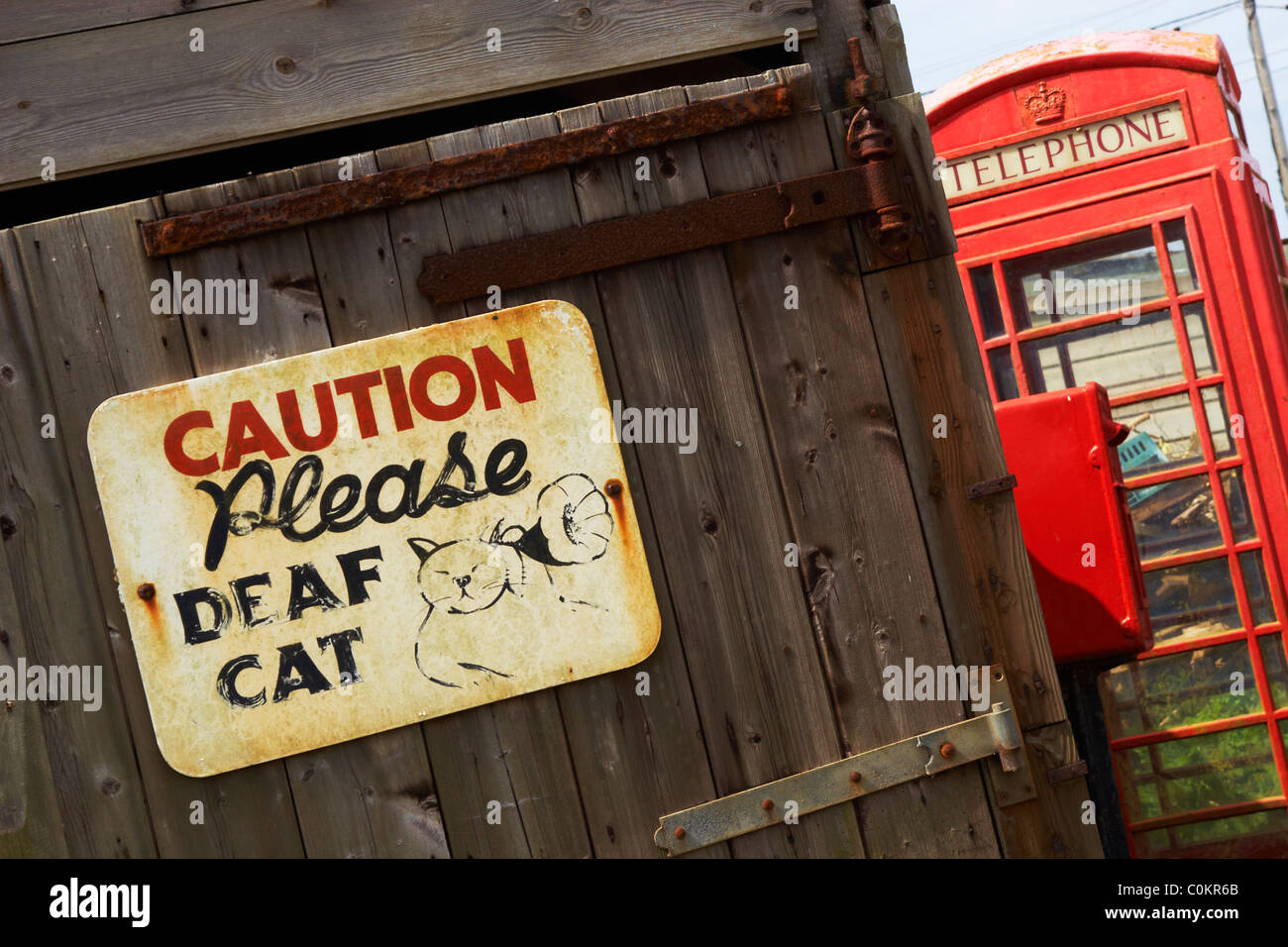 A sign warns of a deaf cat near a red telephone box and post box at Sennen, Cornwall, UK. - Stock Image