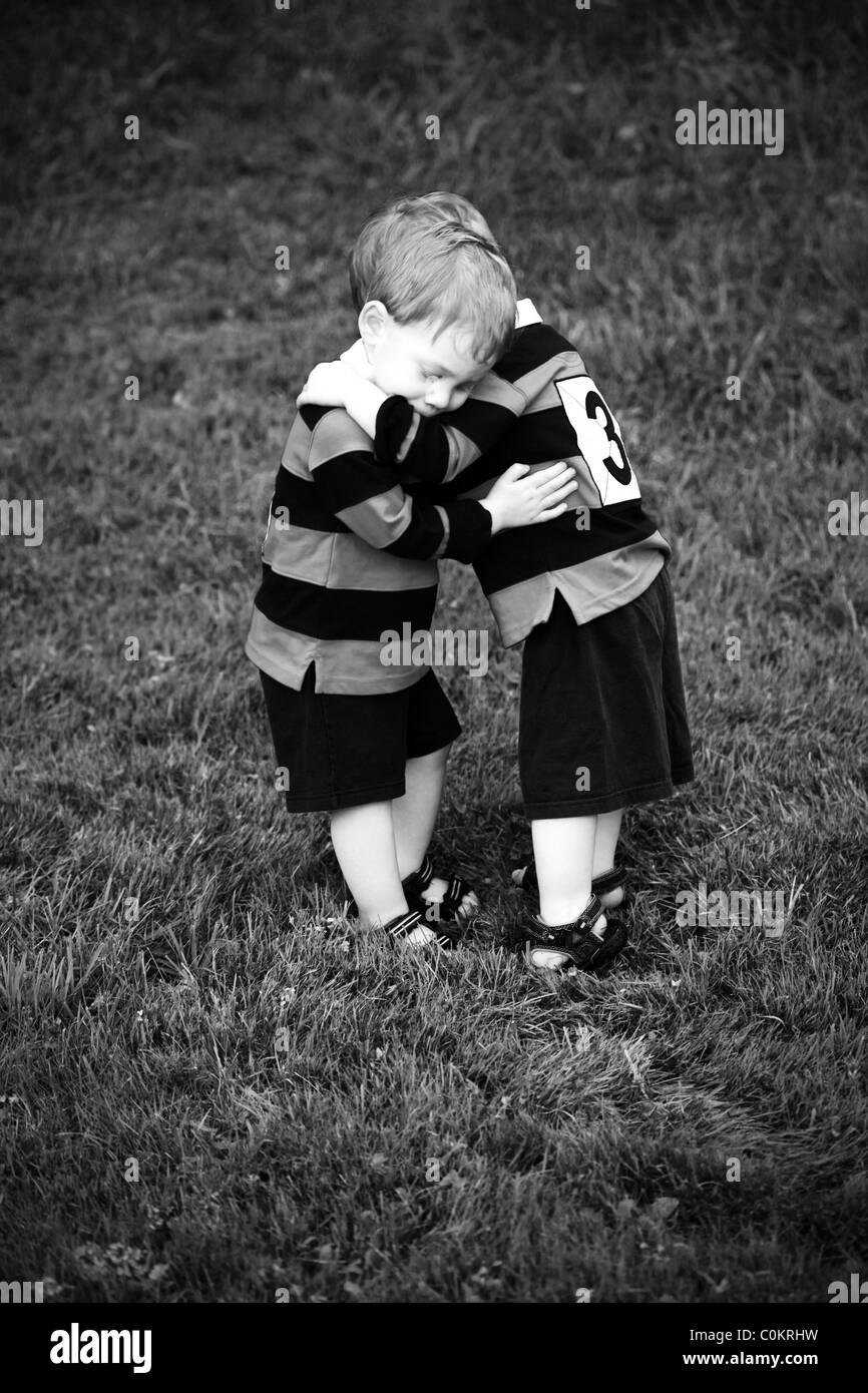 Twin baby boys hugging in rugby clothing - Stock Image