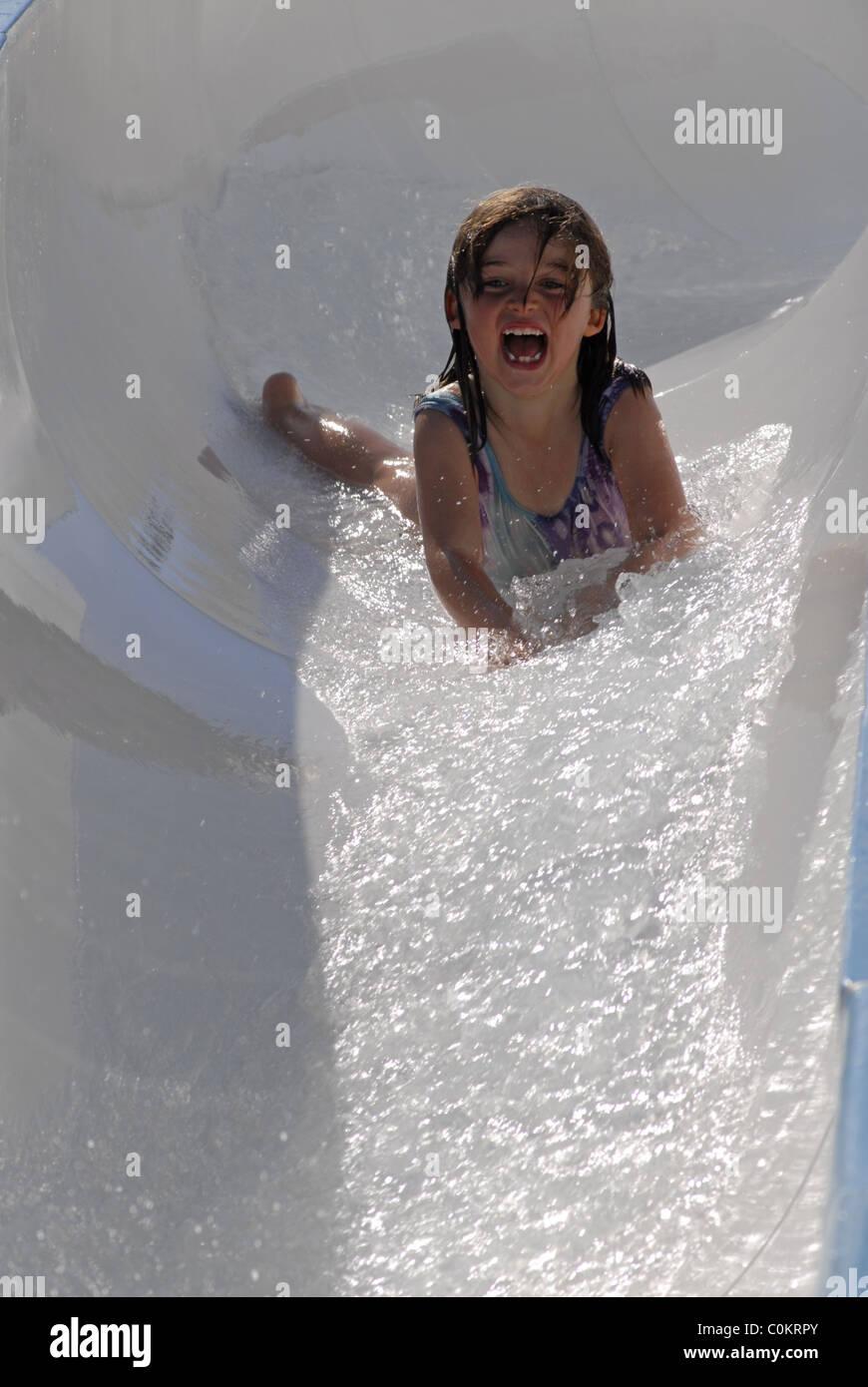 Little Girl Sliding Head First Down A Water Slide Stock