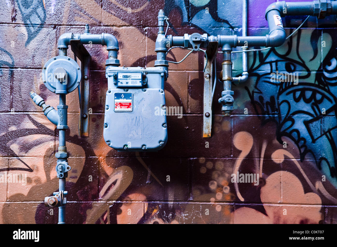 A gas meter and piping against a colorful wall - Stock Image