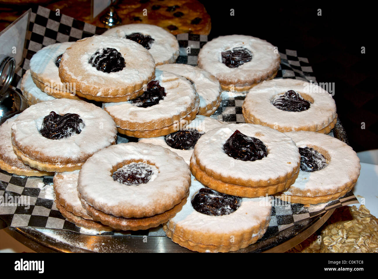 sugar dusted raspberry jam filled cookies piled on platter bakery display Granville Island public market Vancouver - Stock Image