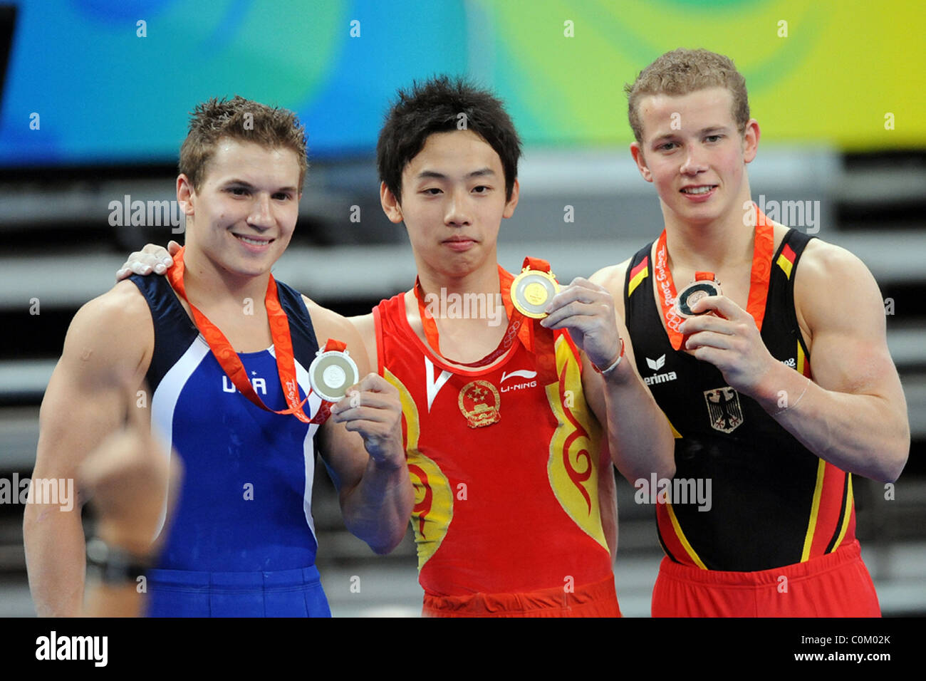 Jonathan Horton of the USA, Zou Kai of China and Fabian Hambuechen of Germany celebrate their medal wins in the - Stock Image