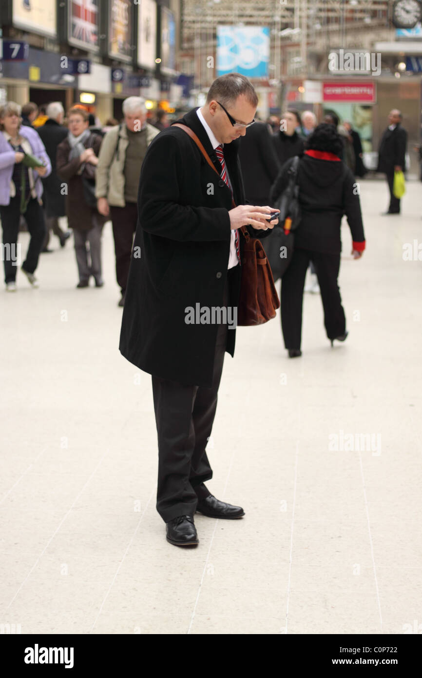 Business man using his mobile PDA device at Waterloo railway station London - Stock Image