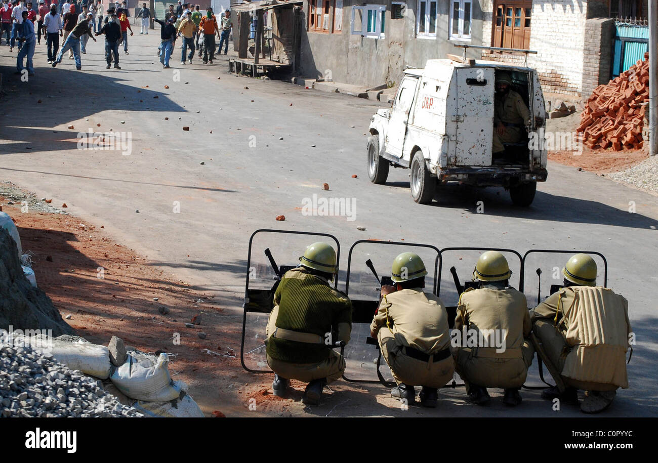 Indian police protect themselves as Kashmiri Muslim protestors throw stones in Srinagar. Hundreds of Kashmiri Muslims - Stock Image