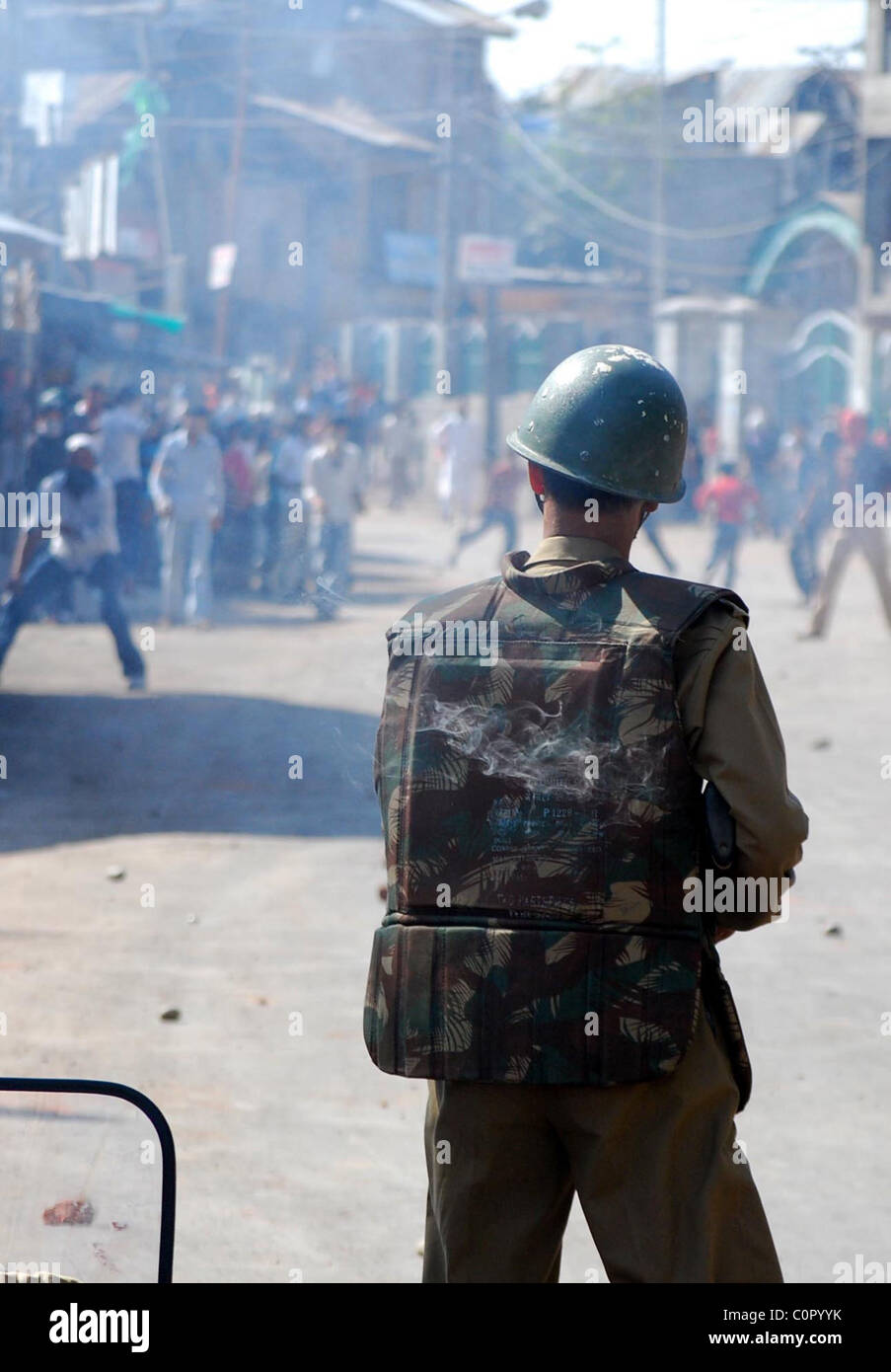 A policeman stands guard as Kashmiri Muslim protestors throw stones in Srinagar. Hundreds of Kashmiri Muslims protestors - Stock Image