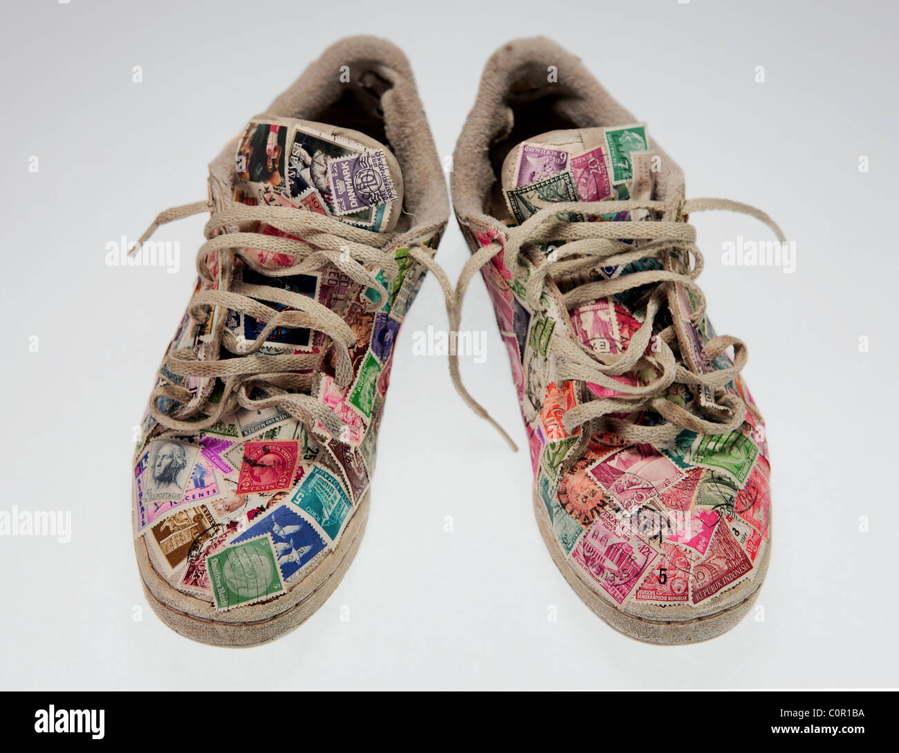 a pair of worn running shoes covered with old postage stamps on a clear background - Stock Image