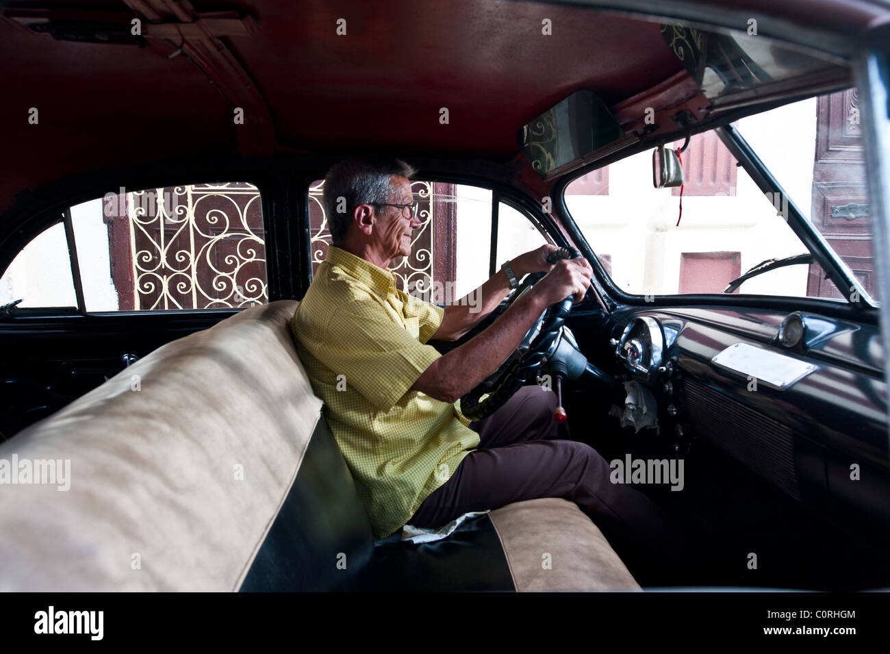 Man in classic american car, Street scene Trinidad central Cuba - Stock Image