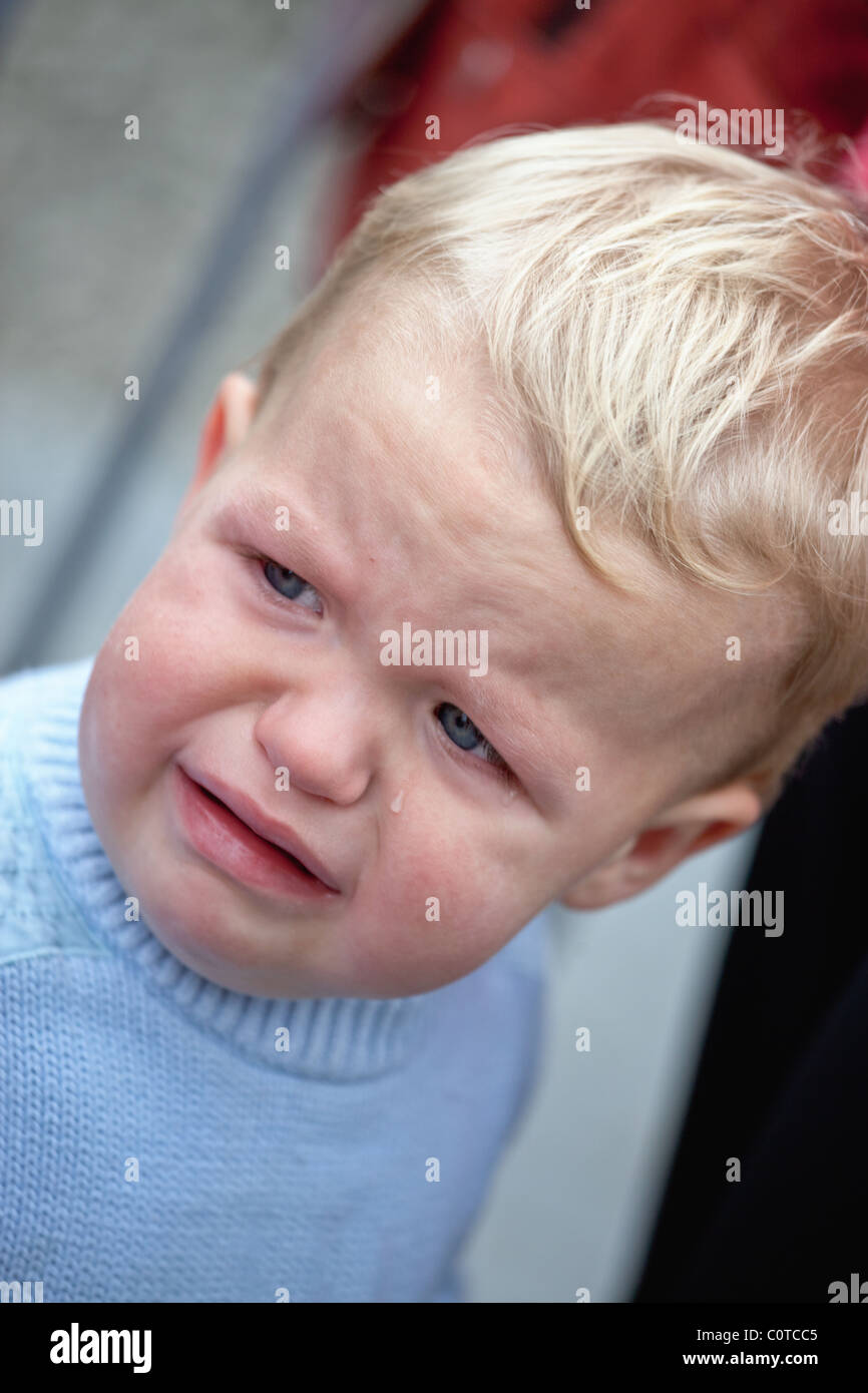 Close-up of crying 2-year-old little boy with a tear on his cheek. - Stock Image