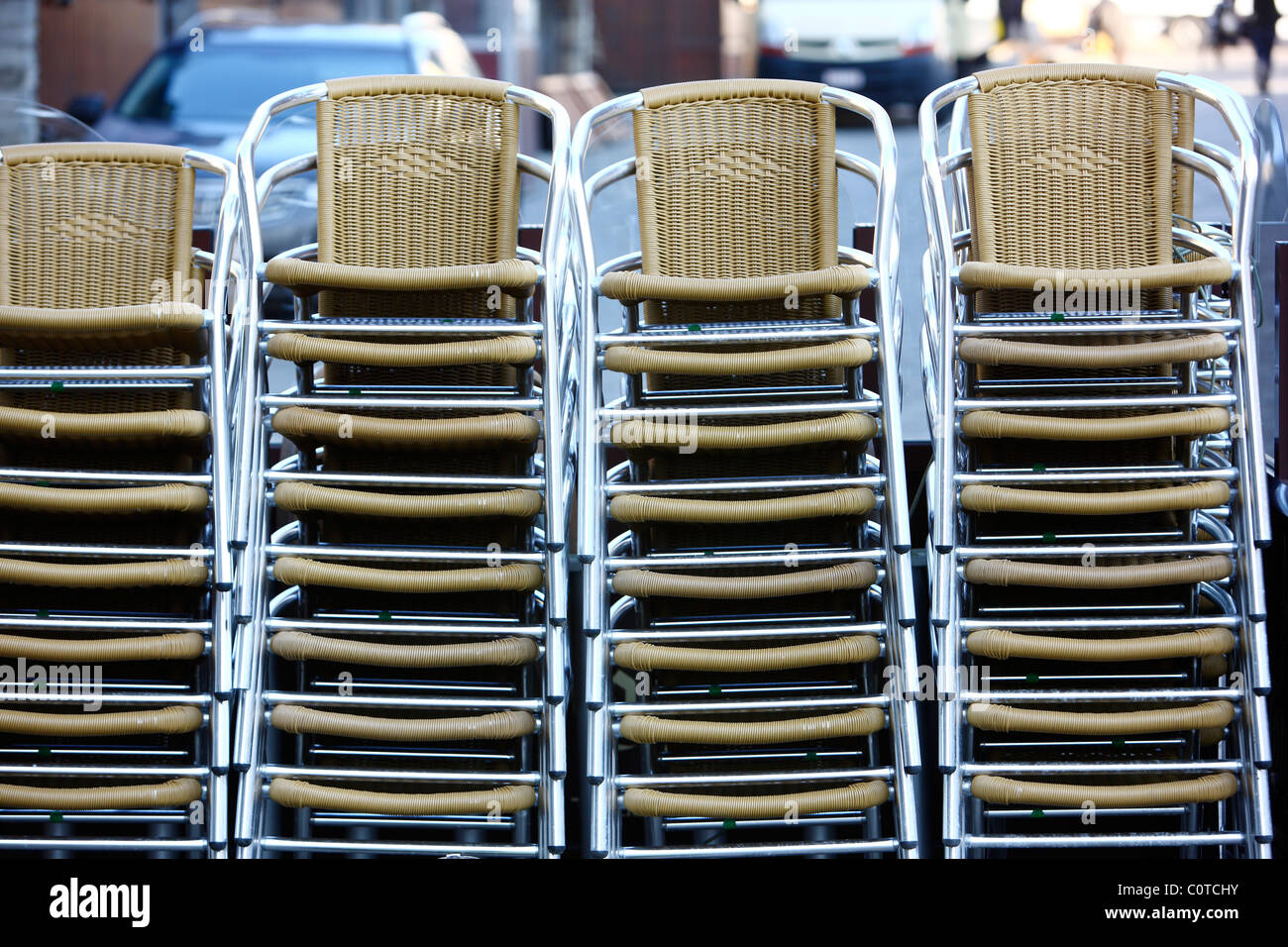 Stacked chairs in front of a bar, cafe, restaurant. Waiting for clients. Stock Photo