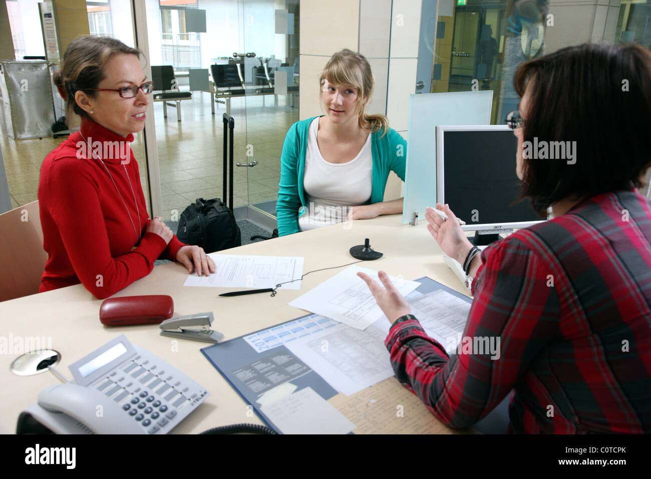 Central patient admission in a hospital. Mother helps her daughter checking into a hospital for a surgery. - Stock Image