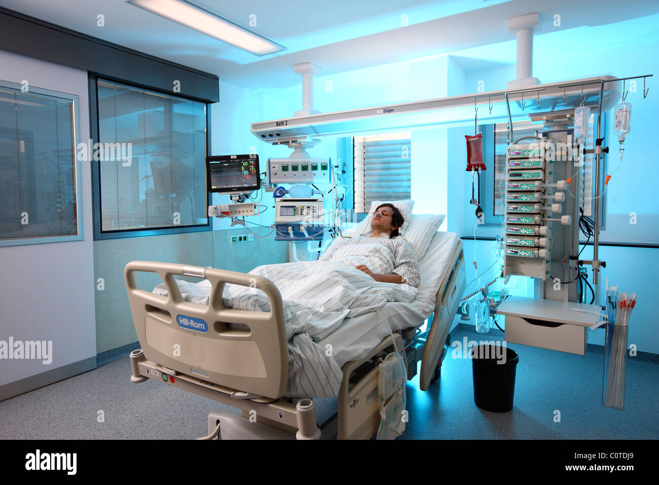 Intensive care unit in a hospital. A patient is connected to different life support systems. - Stock Image