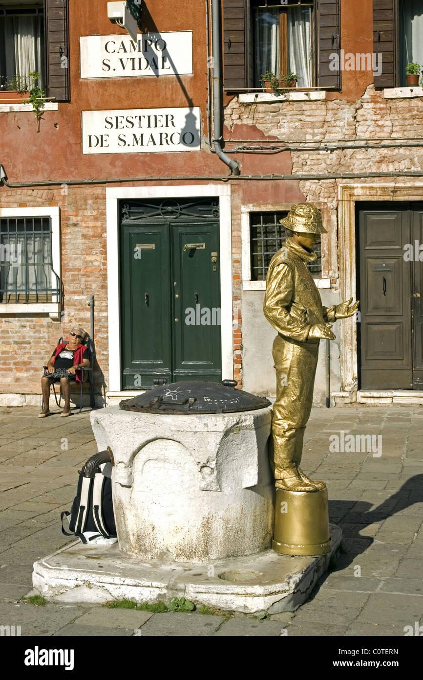 A gold golden mime performs near Academia elderly woman naps sleeps Venice Italy - Stock Image