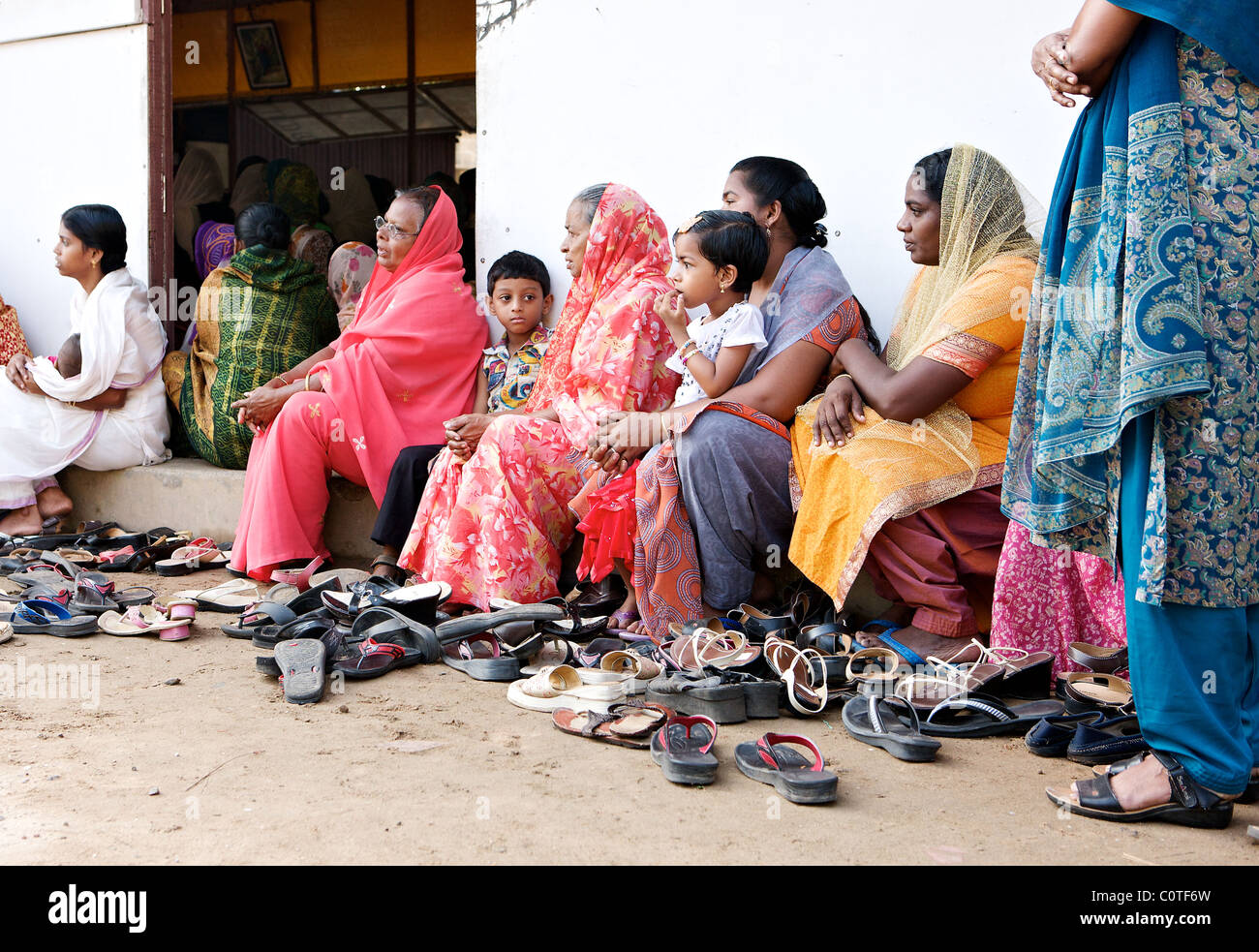 Keralite women and children sit outside a full church in a village outside Cochin, Kerala, India - Stock Image
