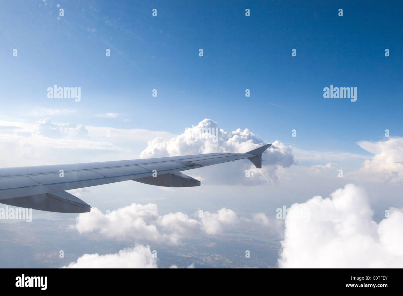 airplane wing aircraft aluminum flying sky in flight on clouds - Stock Image