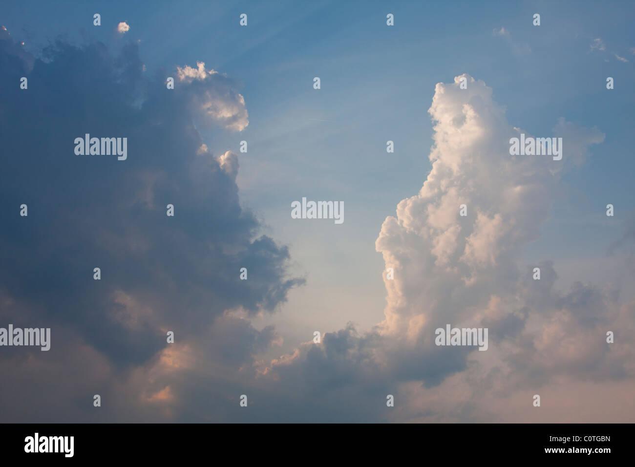 Sunlight breaks from behind a cumulonimbus cloud in the late evening. - Stock Image