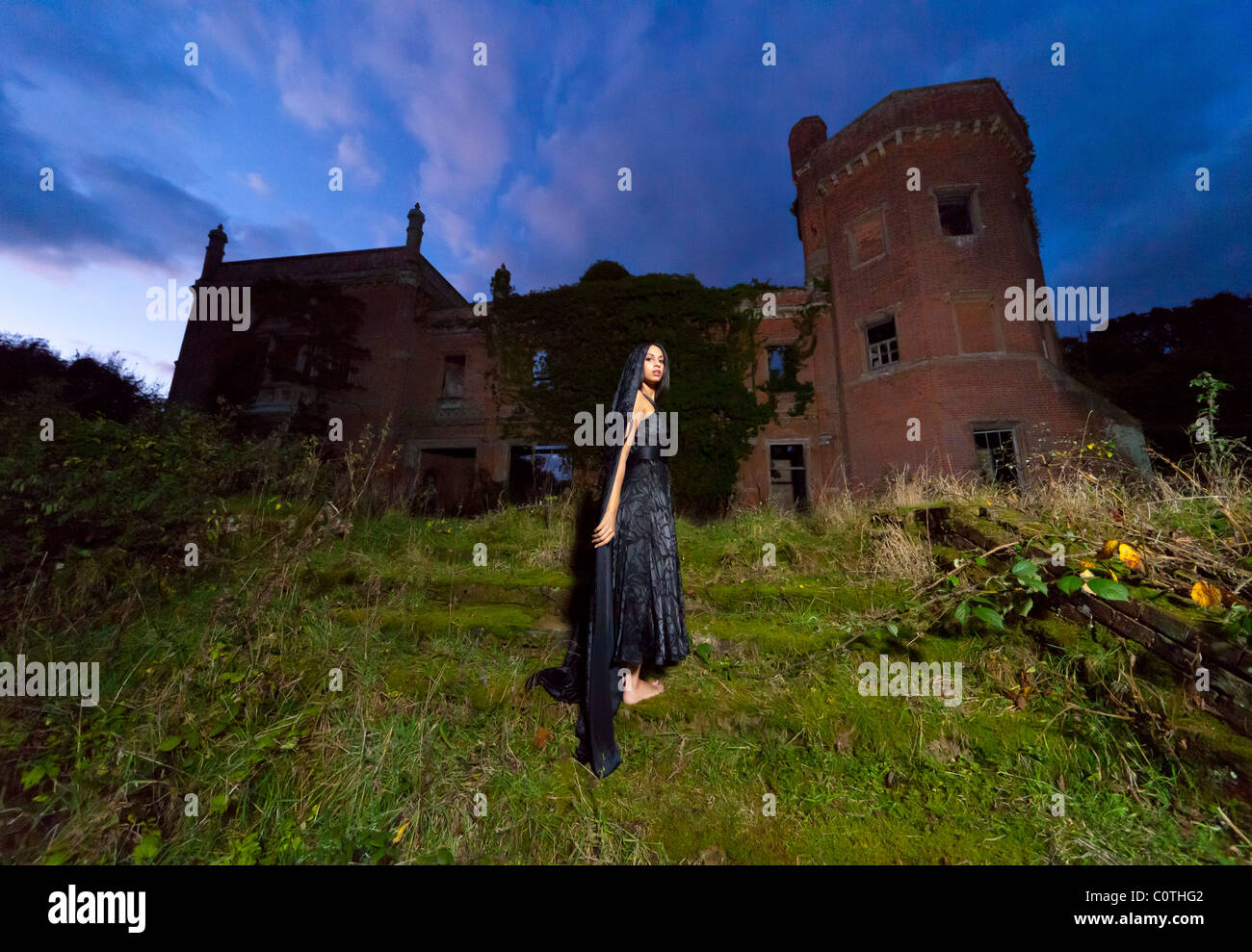 mysterious woman stood in front of an old derelict large country mansion house Stock Photo