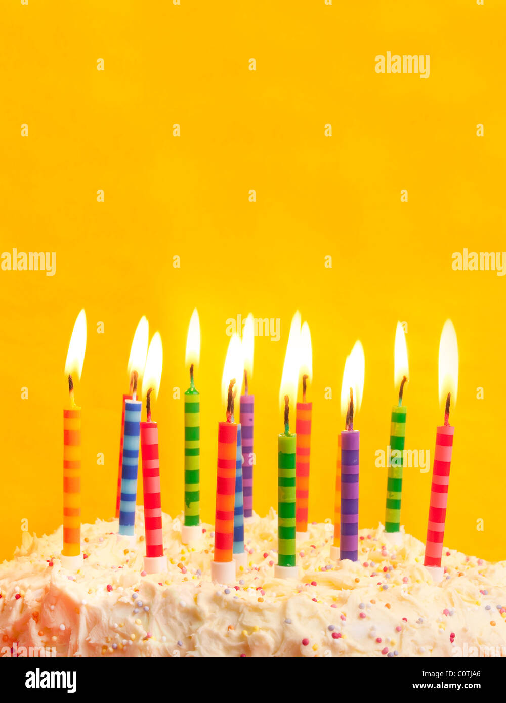 Happy Birthday Cake Shot On A Yellow Background With Candles And