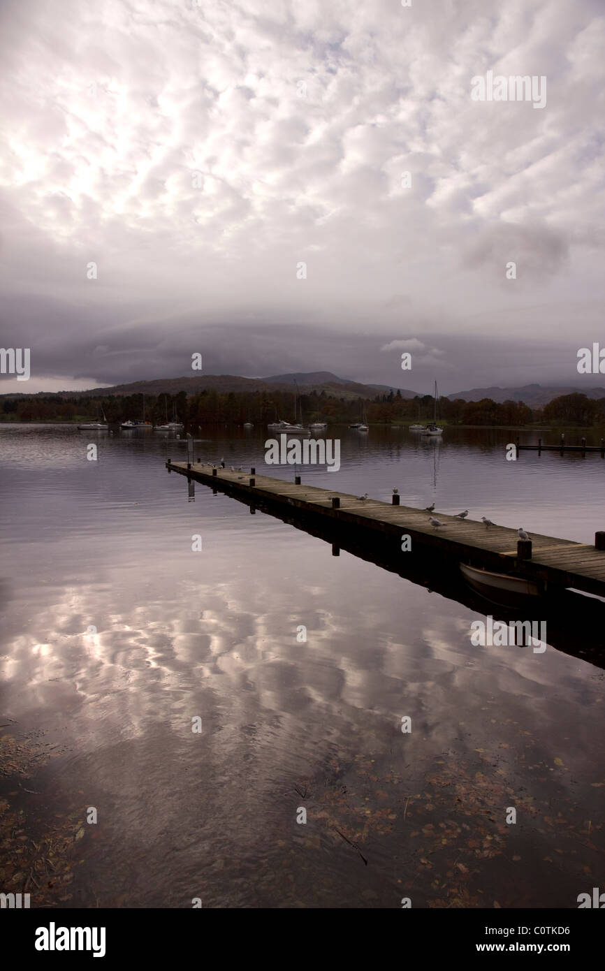Cloudy sky reflections and boat jetty on Lake Windermere, Ambleside, Lake District, Cumbria, England, UK - Stock Image