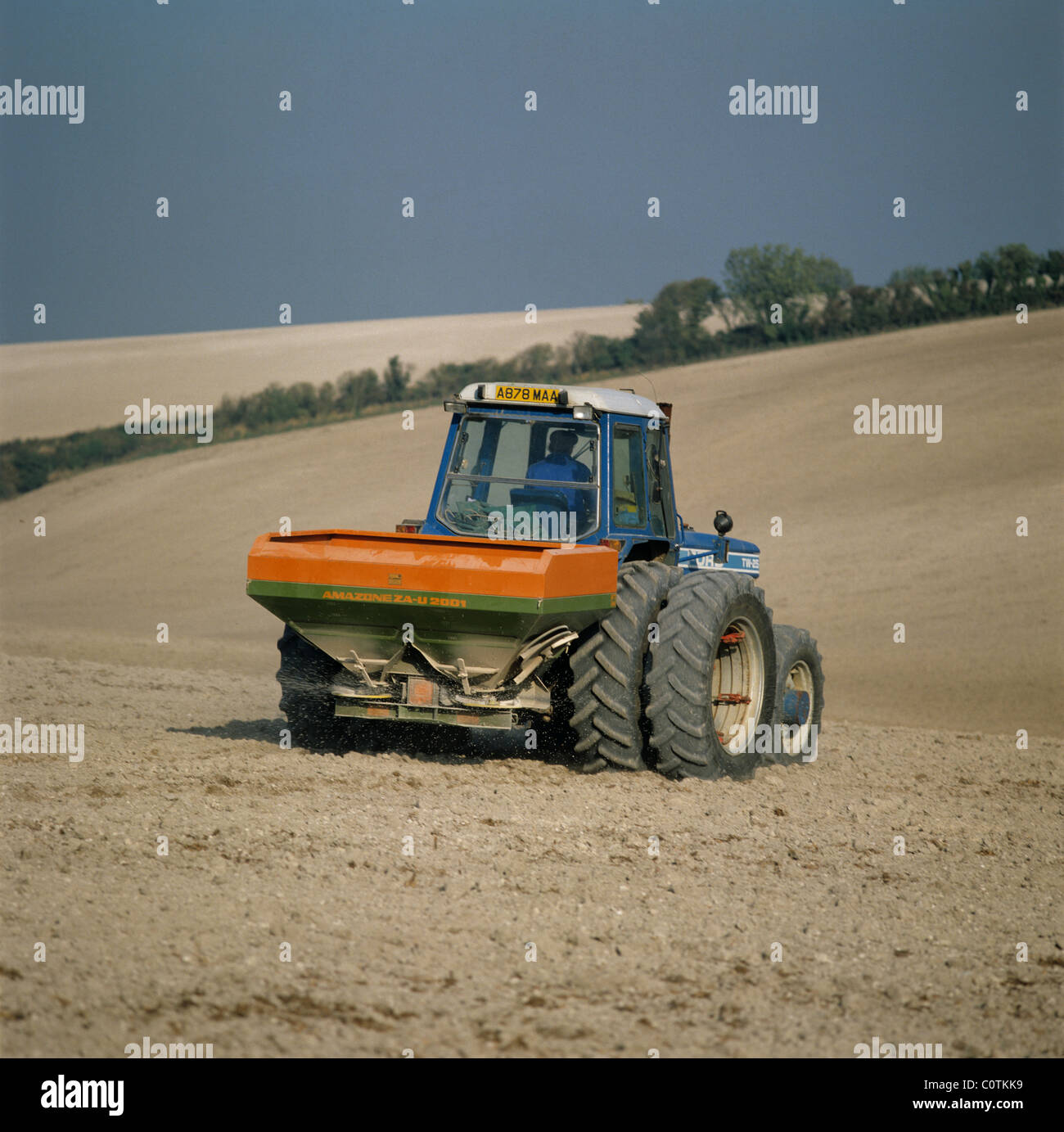 Tractor with Amazone disc spreader spreading fertilizer on a fine downland chalk seedbed - Stock Image