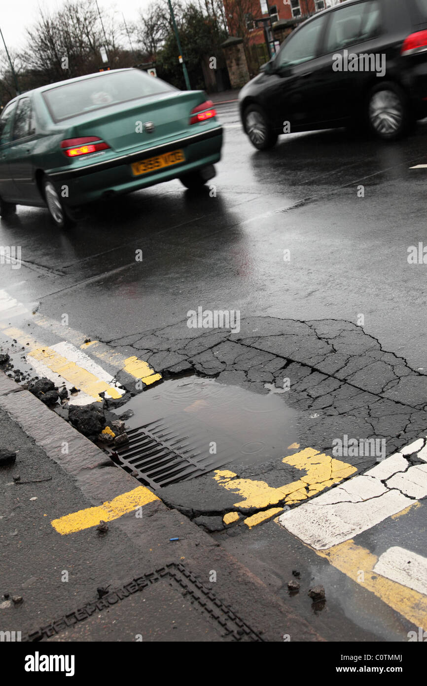 Potholes on a busy U.K. road. - Stock Image