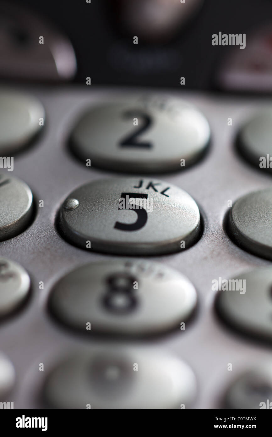 A closeup of a telephone keypad showing the numeral 5 in sharp focus also showing some letters of the alphabet - Stock Image