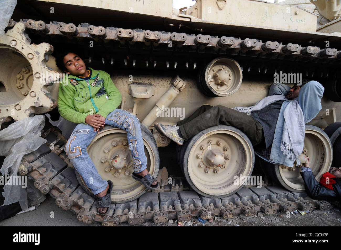 Anti-Mubarak protesters sleeping between the wheels of an Egyptian army tank in Tahrir square in Cairo, Egypt - Stock Image
