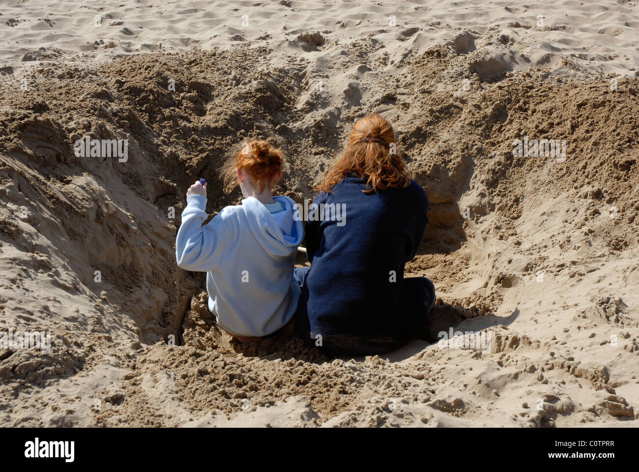 Rear view of two girls digging a large hole on the beach - Stock Image