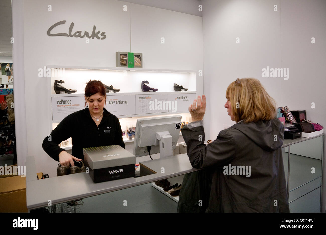 A woman buying shoes at the checkout, Clarks shoe shop