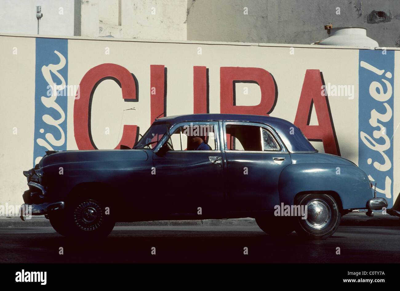 Havana. Cuba. Vintage American car in front of patriotic slogan 'Viva Cuba Libre' in Old Havana. - Stock Image