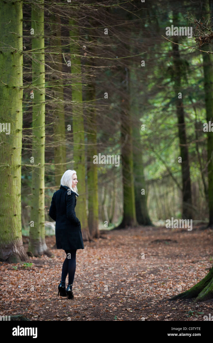 young blonde model in black stiletto shoes and winter coat walking alone through woods in autumn fall - Stock Image