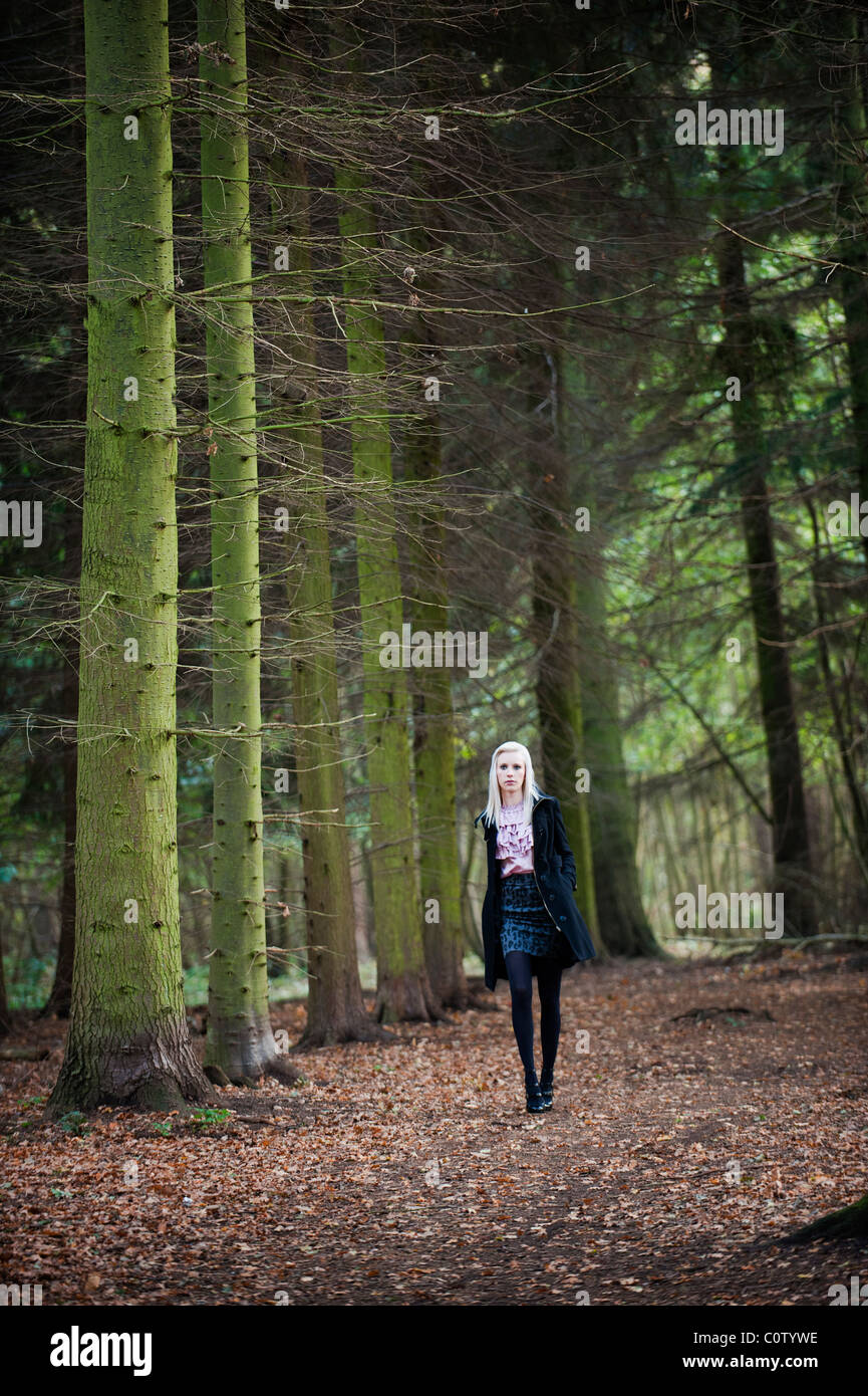 young blonde model in miniskirt and ruffled blouse walking alone through woods in autumn fall - Stock Image
