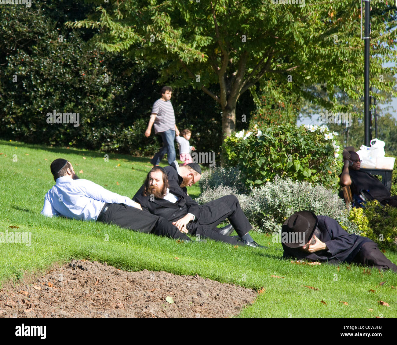 Orthodox Jews relaxing on a sunny  day in the park - Stock Image