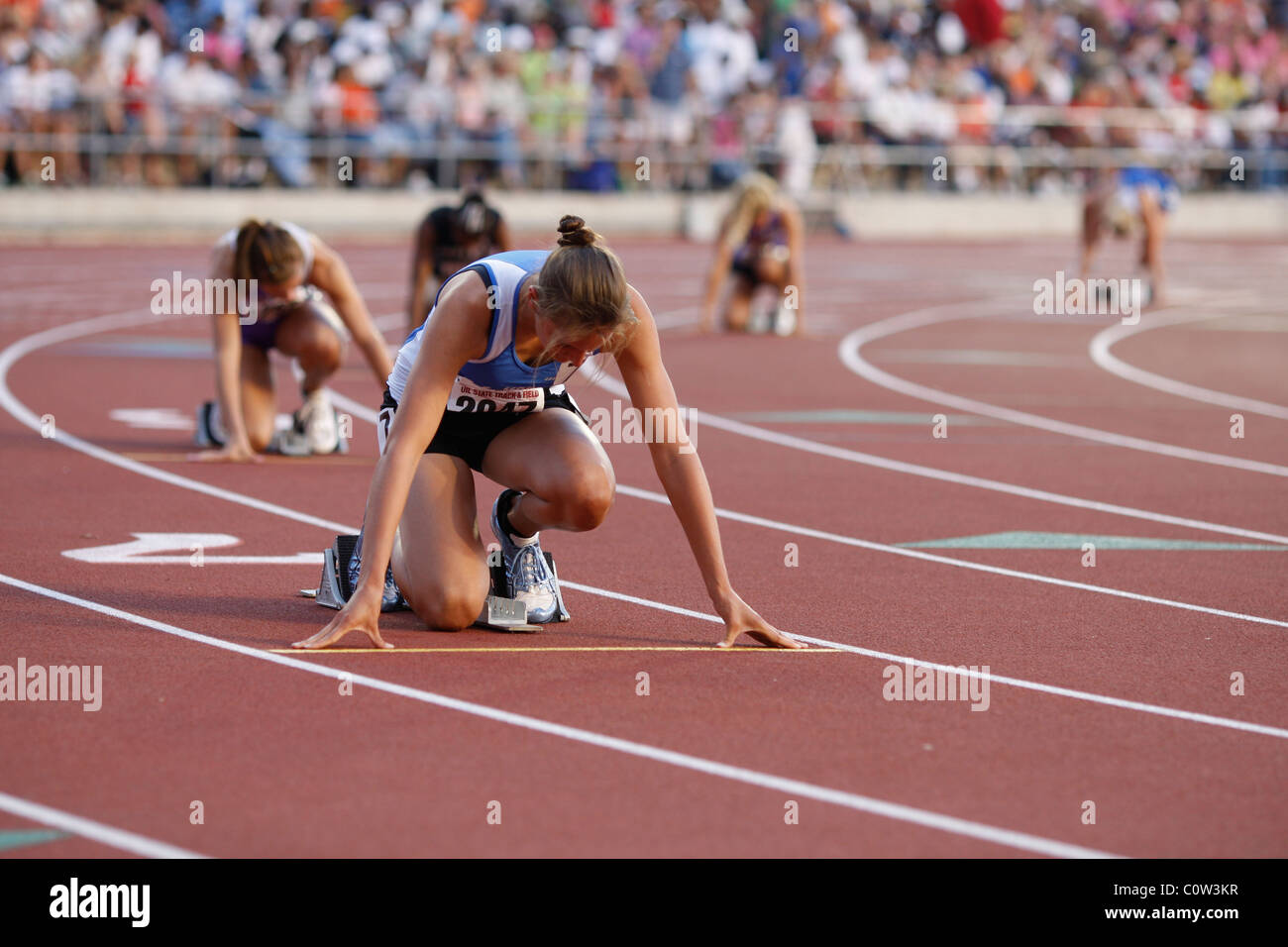 anglo girls in the blocks at the starting line of their race at the