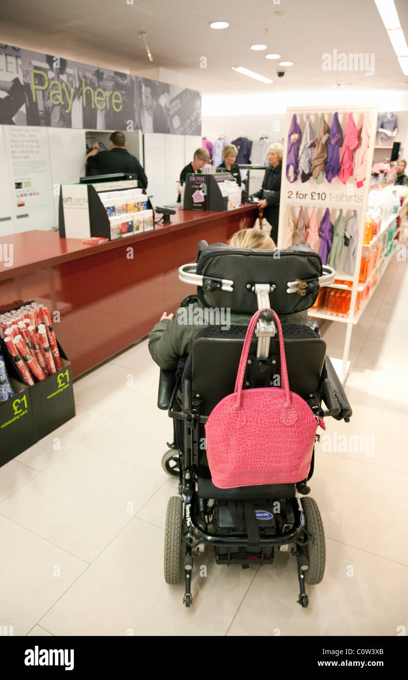 Disabled young woman in a  wheelchair shopping,  UK - Stock Image