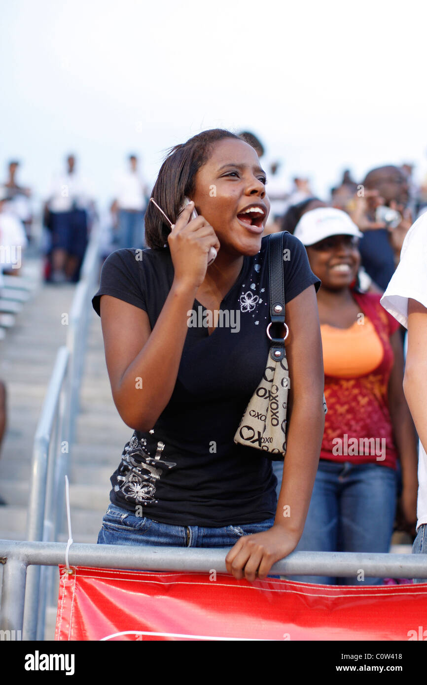 Excited fan talks on cell phone while cheering runners at finish line of race at Texas state high school track championships - Stock Image