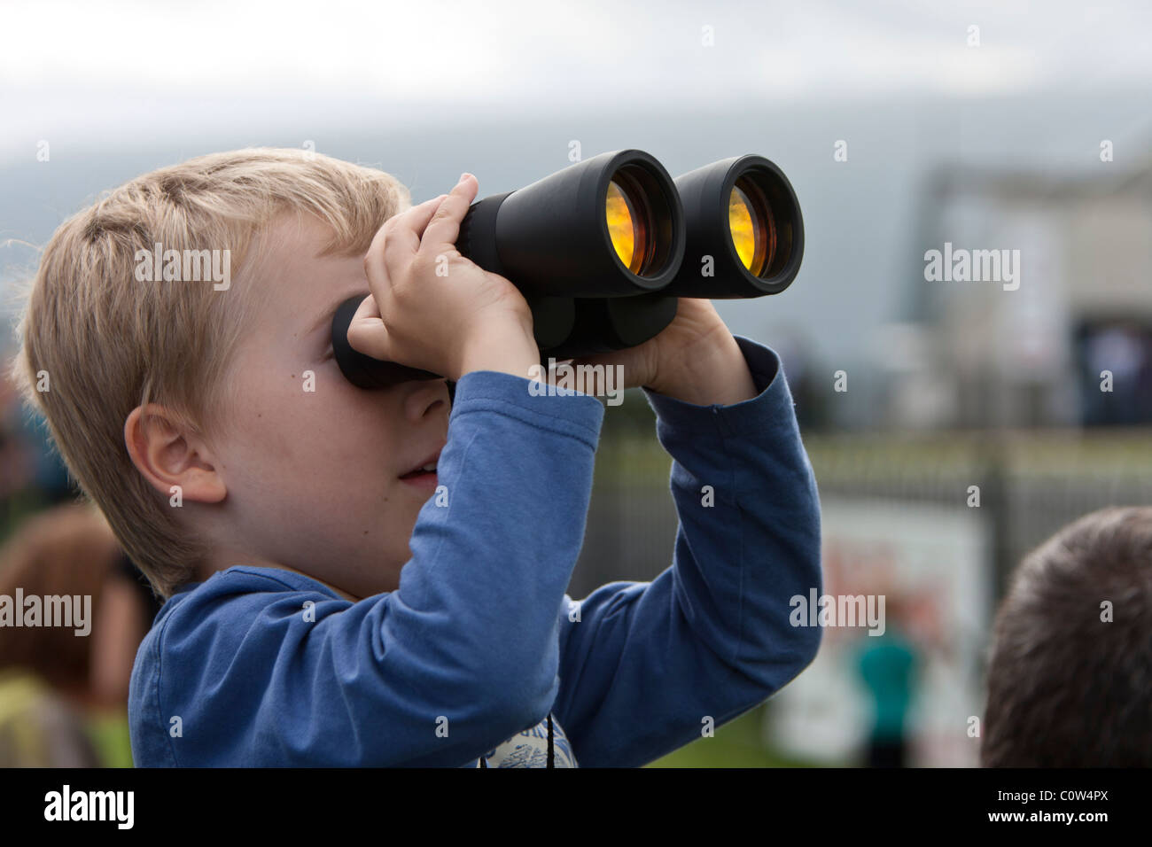 Boy watching the aeroplanes with binoculars  at an airshow - Stock Image