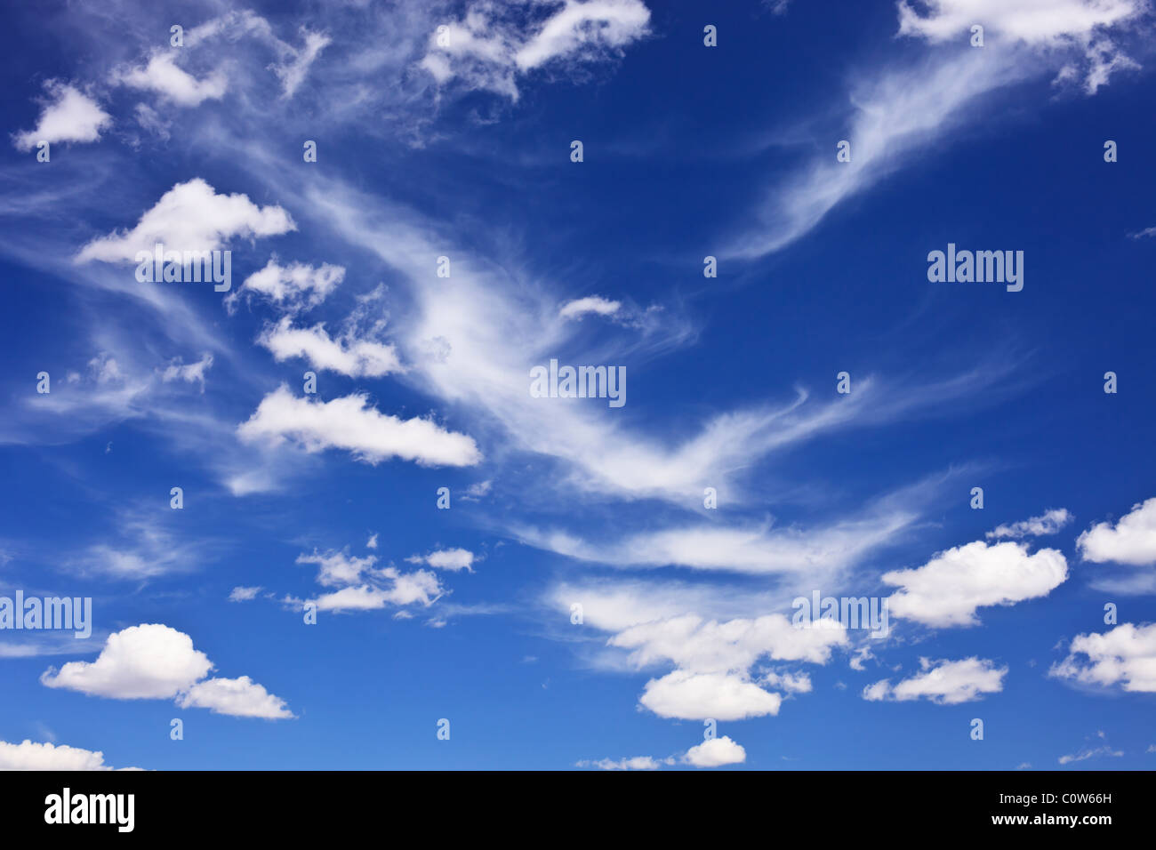 Some scattered and wispy clouds in blue sky over rural western Oklahoma. - Stock Image