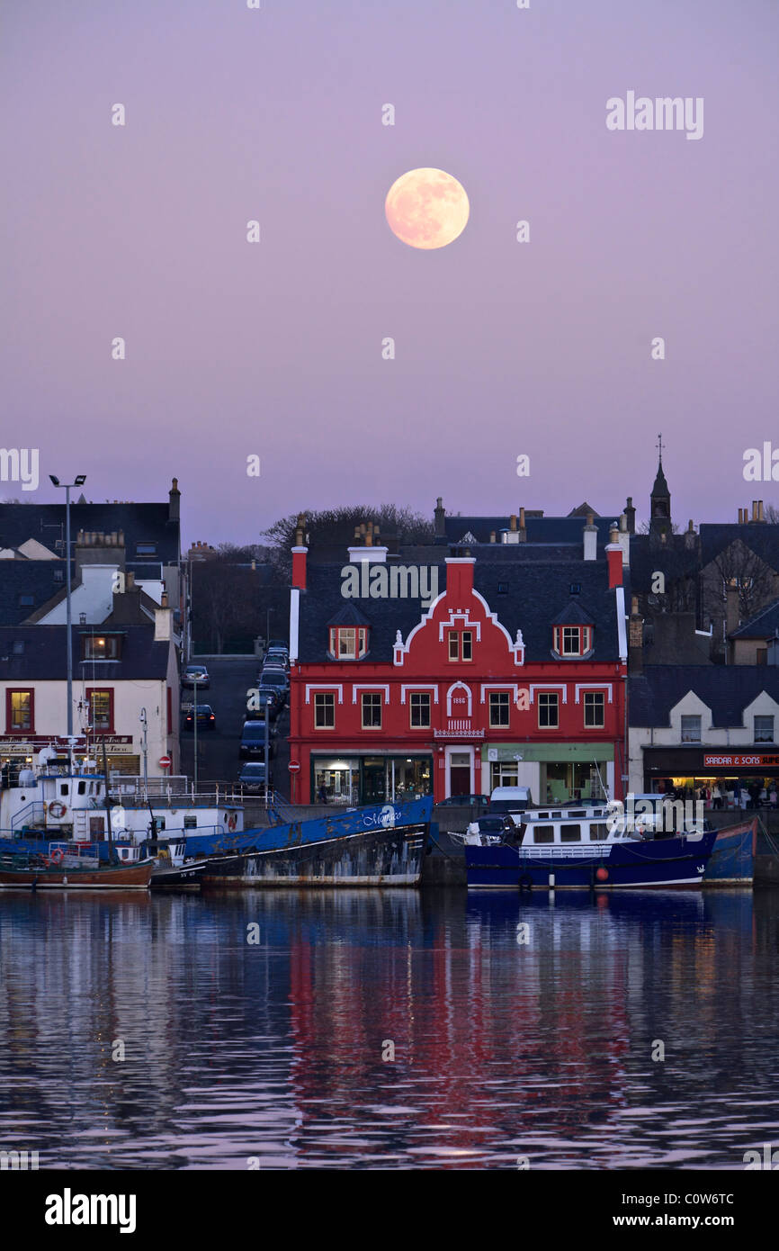 Stornoway Harbour with full moon at dusk. - Stock Image