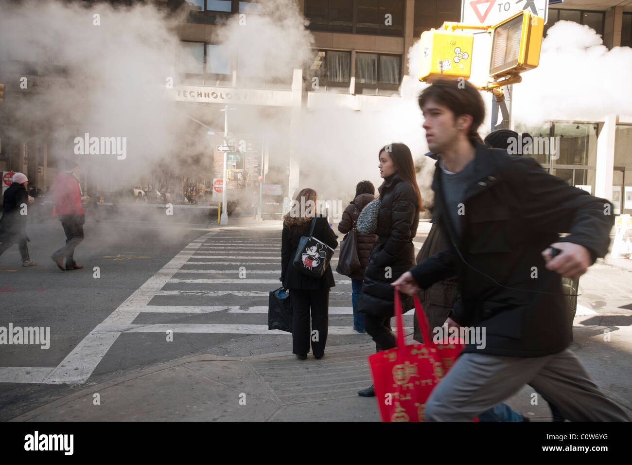 Pedestrians pass by as Con Edison Company vents steam in the Chelsea neighborhood in New York - Stock Image