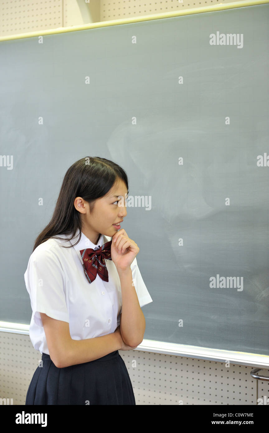 High School Girl Thinking in front of Blackboard - Stock Image
