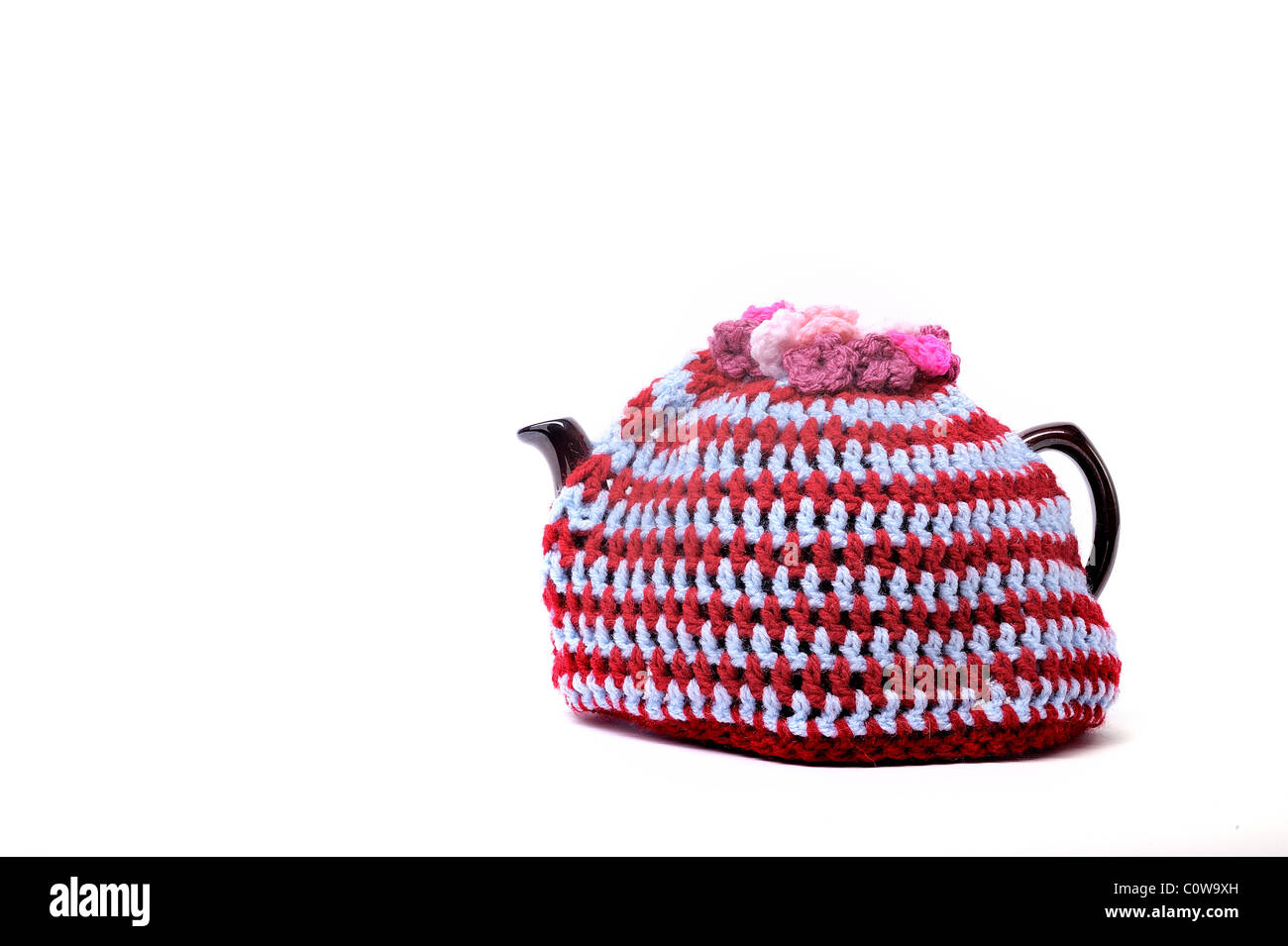 Handmade crochet teacosy in blue, pink, yellow, red, and orange, sitting on top of a teapot, it has flowers on the - Stock Image