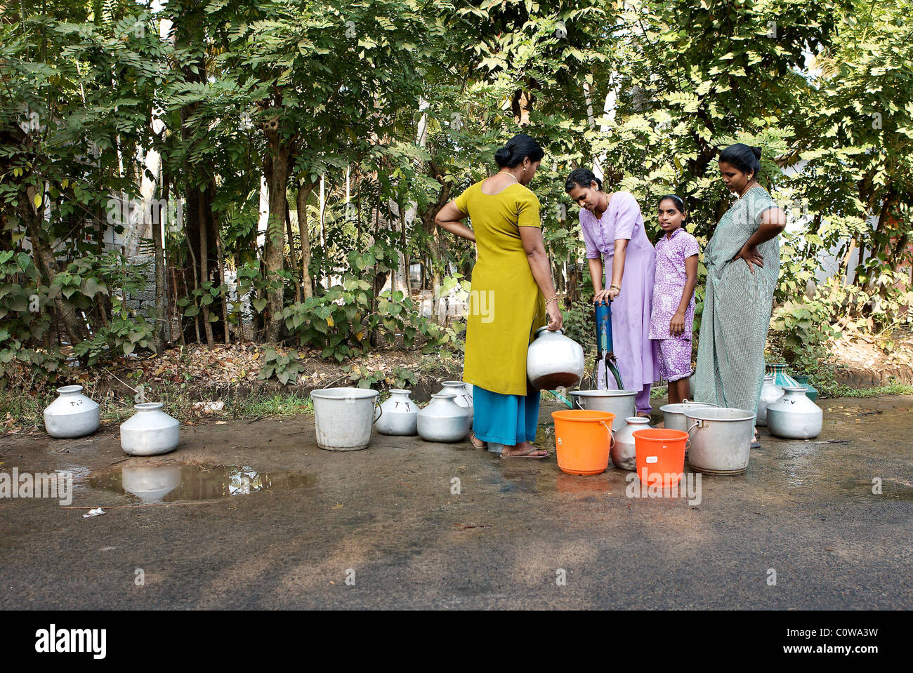Women collect fresh water from a road-side water pump in a small village south of Kochi, Kerala, India - Stock Image