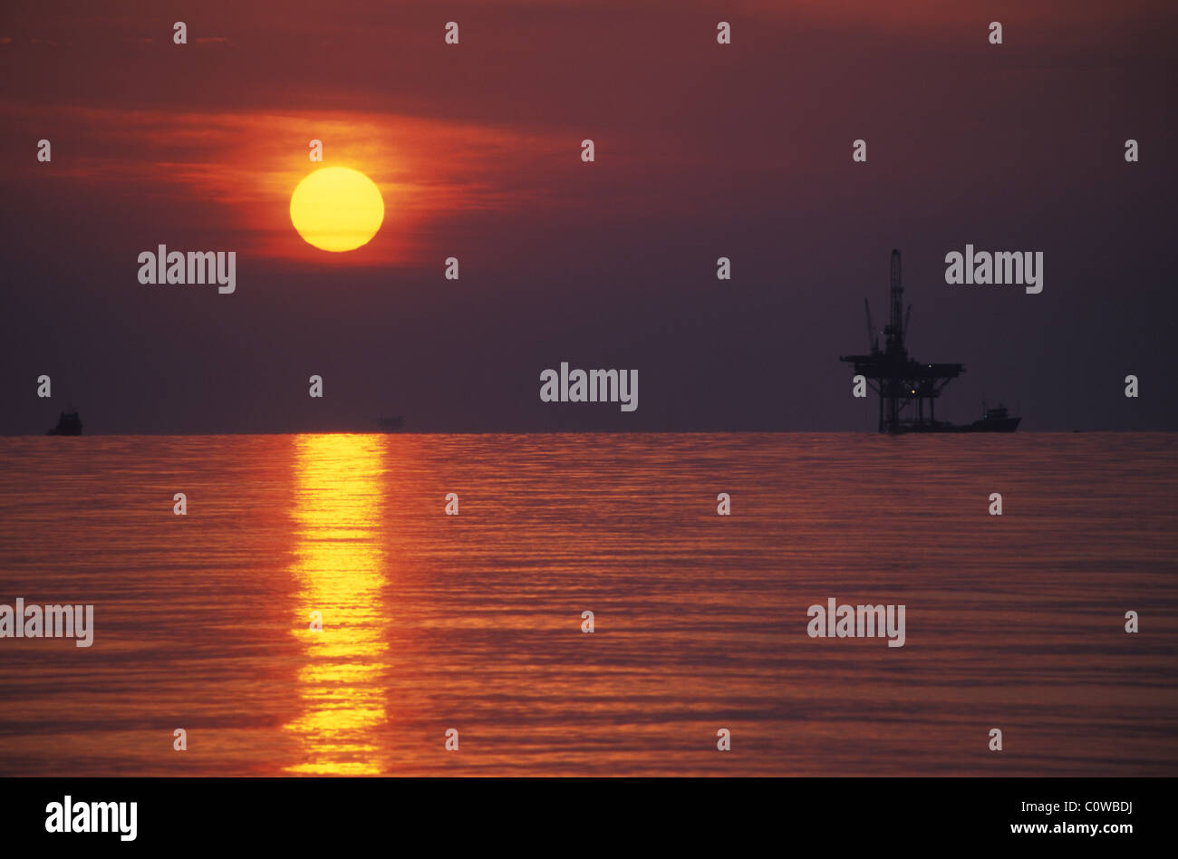 An off-shore oil rig at sunset. - Stock Image