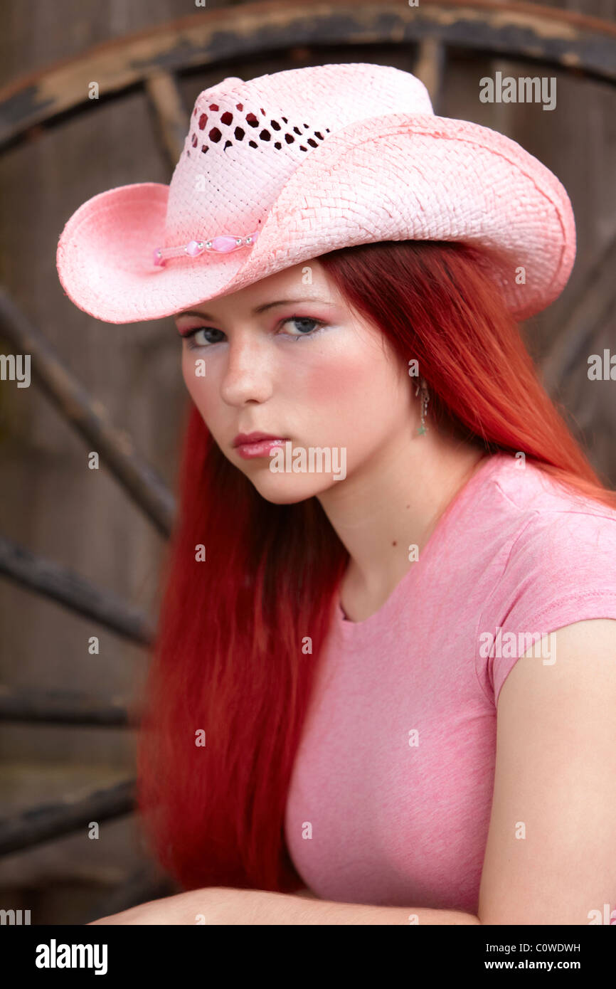 762e4779d8b A young teenage girl with dyed red hair wearing a pink cowboy hat - Stock  Image